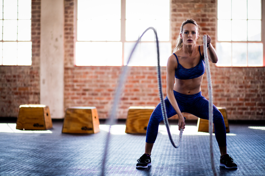 Athletic young adult girl focused on a fitness training with ropes at the gym